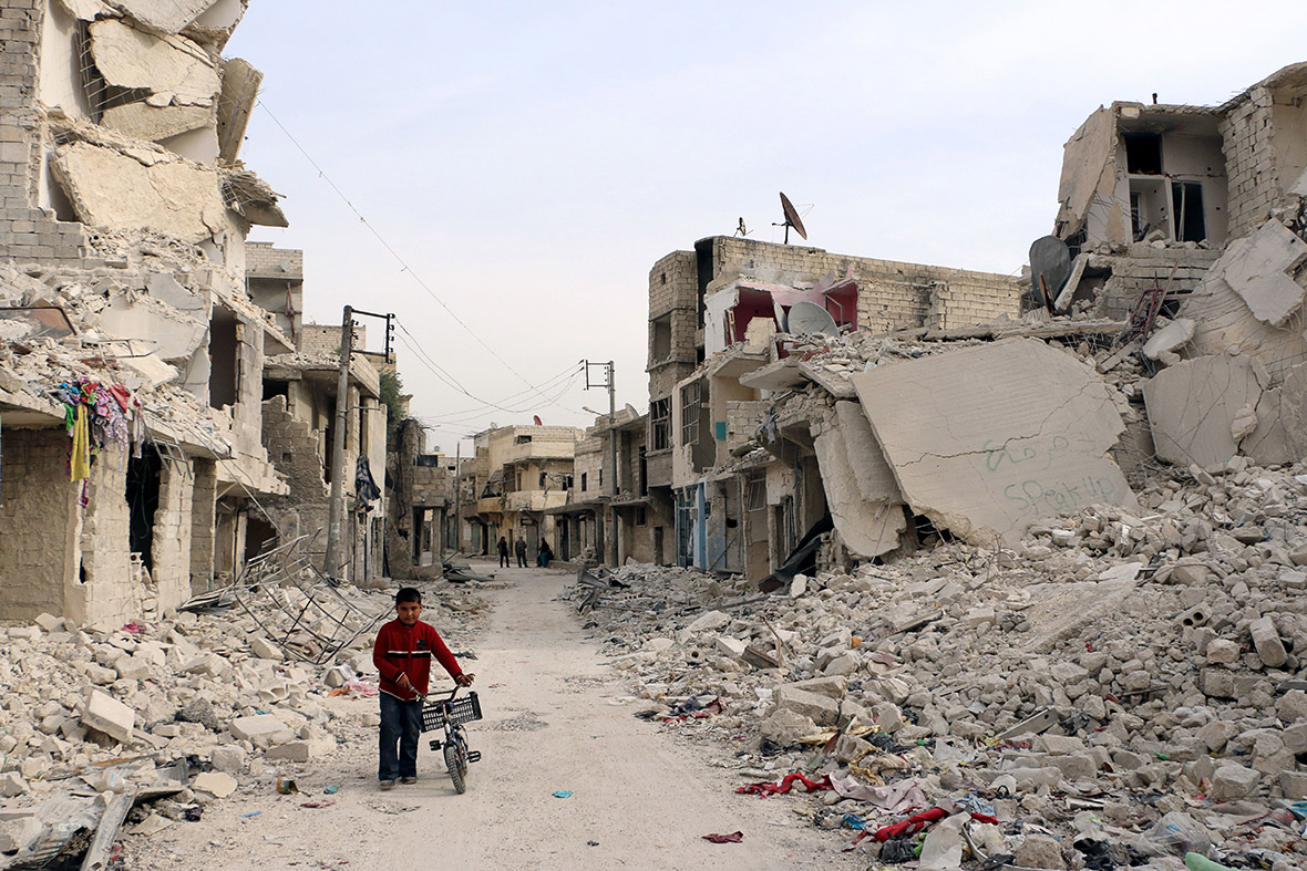 A Syrian boy walks with his bicycle in the devastated Sukari district of Aleppo on 13 November, 2014AFP